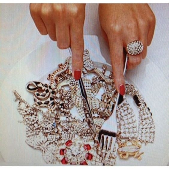 Young woman cutting jewellery on plate with fork and knife, close-up Photo by Serge Krouglikoff on Getty Images